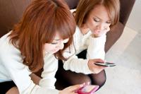 携帯端末を操作する女性たち